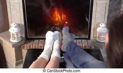 Moving legs of couple in woolen socks heat up near fireplace...
