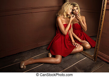 Fashionable woman in red dress with lipstick and gold mirror