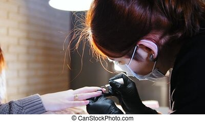 Working manicurist - nail master in medical mask doing professional manicure