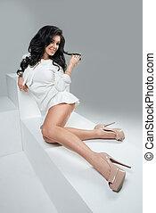 Fashionable elegant brunette woman posing in dress, looking...