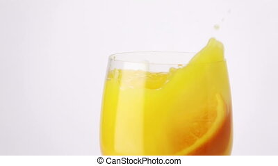 Slice of Orange Falling into a Glass of Orange Juice. -...