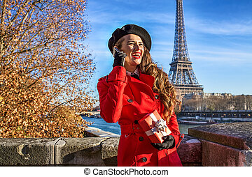 woman in Paris using a mobile phone and holding present box...