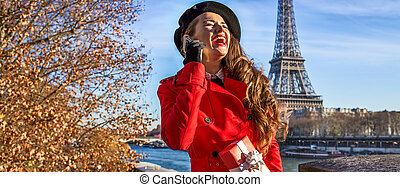 woman in Paris using a cell phone and holding present box -...