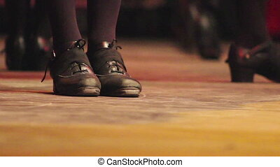 Woman dancing Irish dance on stage with traditional step shoes