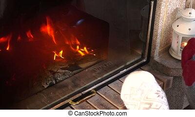 wiggling feet in woolen socks heat up near fireplace -...