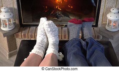 Moving feet in woolen socks heat up near fireplace - Moving...