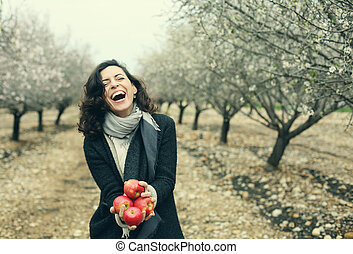 Outdoor portrait of 40 years old woman holding red apples