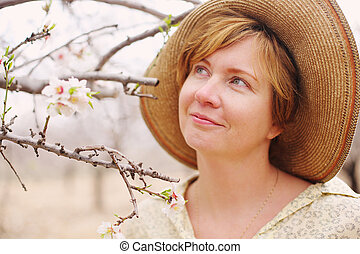 Happy woman in spring blossom park. soft backlight