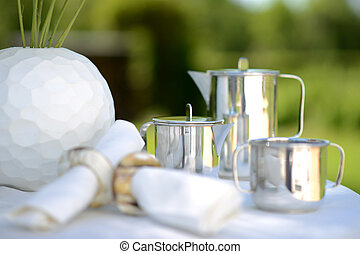 Coffee outside - Luxury silver coffee pot on a linen covered...