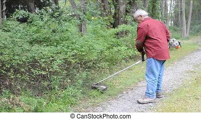 senior using weed whacker - senior man using weed eater...