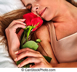 Woman sleeping in bed. Girl lying on bed with flower.