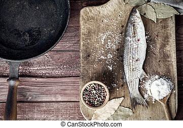 Fresh fish smelt with spices on the kitchen board, near the...