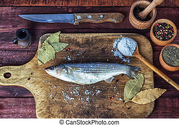 Fresh fish smelt for cooking on a kitchen board, near spices...