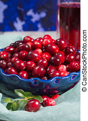 Red cranberry juice in a glass, cranberries in the blue clay...