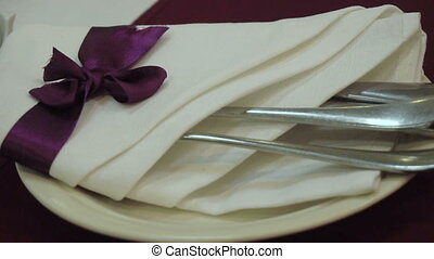 girl takes a beautiful cutlery napkins with a purple bow -...