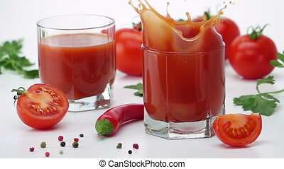 Ripe Tomato Falls into a Glass of Tomato Juice.