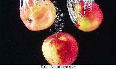 Ripe Apples Falling Through Water. Dark Background. Slow...
