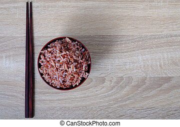 Top view stream brown rice in bowl and chopsticks on wooden...