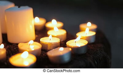 Tea light candles being blown out in the dark forest at...