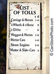 Toll list - Old white sign showing toll road prices.
