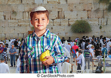 Cute boy in skullcap with the etrog - Sukkot at Western Wall...