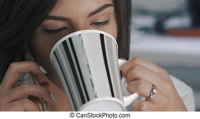 Close up of young business woman speaks mobile phone and drinks coffee at office