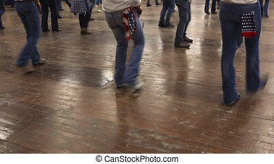 People dancing line dance country music with cowboy boots
