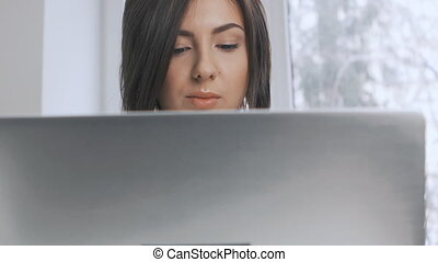 attractive businesswoman in a white shirt works at a laptop in the office