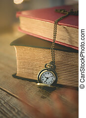 close-up old pocket watch with stack of book on morning light in vintage tone, for new day new life concept