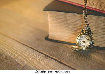 close-up old pocket watch and stack of book with copy space on morning light in vintage tone, for new day new life concept