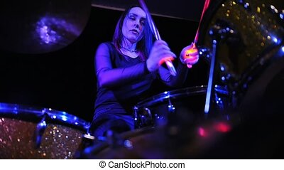Attractive girl playing electronic drums on stage. Concert -...