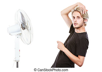 Young man fighting with wind from cooling fan - Air...
