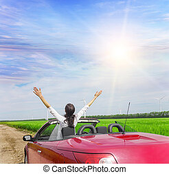 Woman in a red cabriolet in a field with wind power. - Woman...