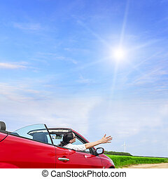 Woman in a red carin a field with wind power. - Woman in a...