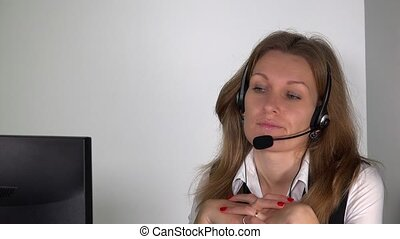 confident female customer service consultant with headset in front of computer