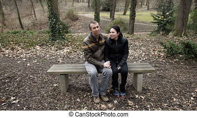 Couple on Park Bench Talking in Early Spring - A male and...