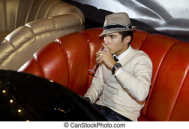 Man on sofa in night club - Man with hat seated on sofa in...