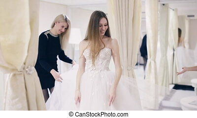 Young woman chooses a wedding dress in bridal shop - Pretty...