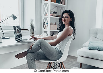 Surfing the net at home. Beautiful young woman using laptop...