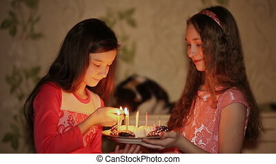 Two teenage girls lighting candles on birthday