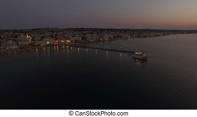 Flying over touristic boat in sea at night - Aerial view of...
