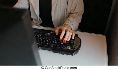 Man play video game using keyboard with red buttons