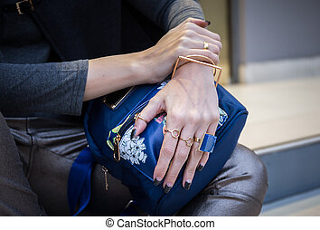 woman hands with fau bijou on blue bag - woman hands with...