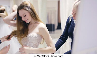 Pretty girl trying on wedding gown in fitting room - girl...