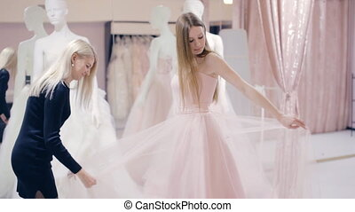 Cute girl trying on prom dress in shop - girl chooses a prom...