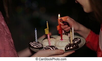 Two teenage girls lighting candles on birthday. Cake with...