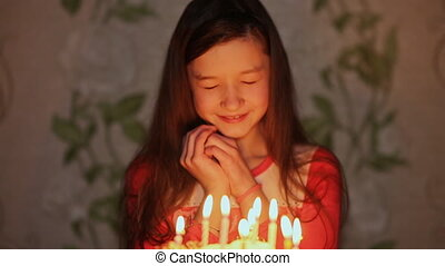 Girl closing her eyes make a wish and blows out the candles...