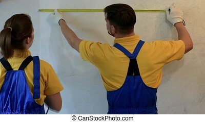 Two adult repairmen in blue coveralls make measurements with...