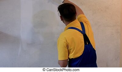 Male painter in blue coveralls painting the wall with white...