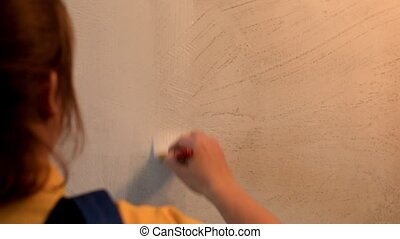 Female painter holding paintbrush with white color and painting the wall.